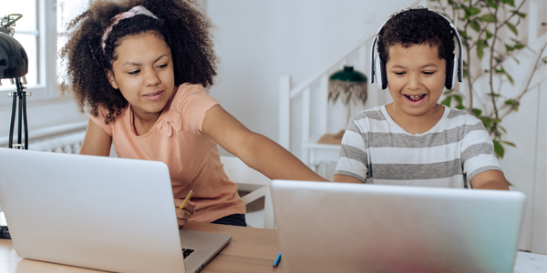 Two kids using cyber safe techniques on their laptops