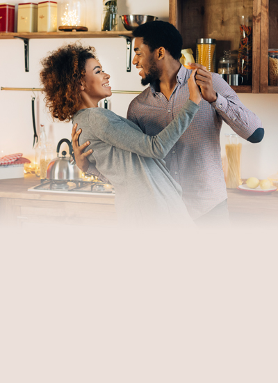 Two people dancing in a kitchen