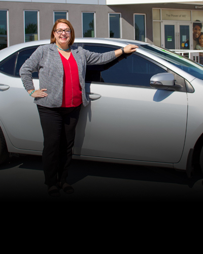 Person standing in front of a white car outside of Nusenda