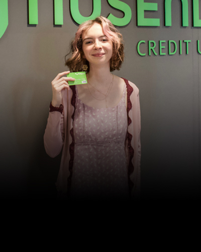 Young person at a Nusenda Credit Union branch holding a debit card.