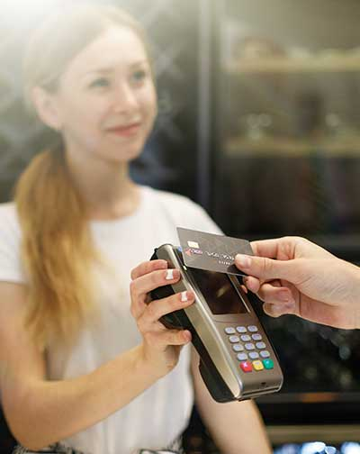 Woman sales clerk with customer using contactless card technology