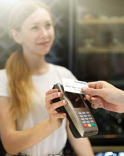 Woman holding a credit card machine to a contactless card