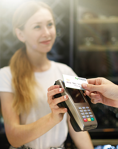 Woman holding credit machine to contactless Nusenda card