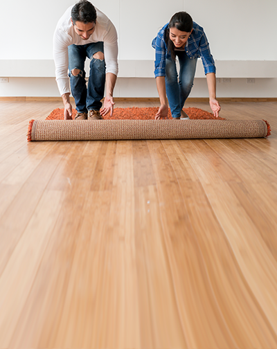 Couple unrolling a rug on a wood floor